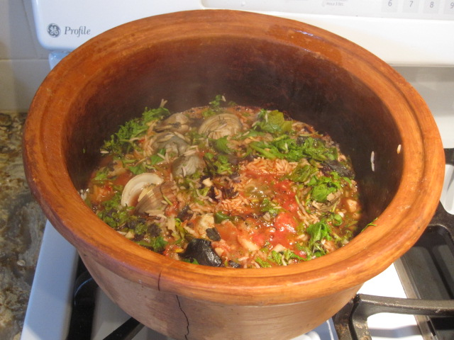 One pot dish featuring rice, greens, clams, tomato paste & spices -- flavors magically blend. Tasty and super easy to make.